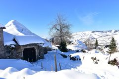 Mountain village with ancient palloza houses covered with snow. Snowy mountainside and spruces, blue sky, Piornedo, Spain. royalty free stock photos