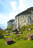 Mountain village with church and waterfall, Alps, Switzerland . Stock Photos