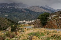 Mountain village on a cloudy day. Countryside. View of the valley, village and mountains in the distance on a cloudy evening Greece, island Crete Stock Photo