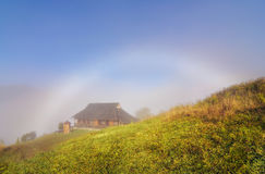 Mountain village in the fog with white rainbow Royalty Free Stock Photos
