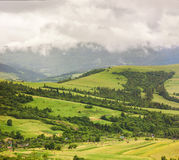 Mountain village on green hill under heavy rainy clouds Royalty Free Stock Images