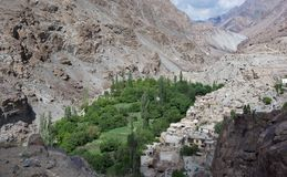 Mountain village, among the high rocks on the bottom of the gorge is green patch of trees and white peasant houses near the cliff, Royalty Free Stock Images