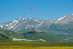 Mountain village and meadow. In the Piano Grande, Italy with paraglider above Stock Image