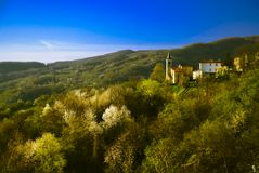 Mountain village in Parma. Location is Parma, Italy. Mountainous region with a village perched on a ridge surrounded by lush forest vegetation. Blue skies above royalty free stock photo