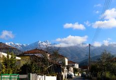 Mountain village road in the Peloponnese Pennisula of Greece with snow covered fog shrouded mountains in the background.jpg. A Mountain village road in the Royalty Free Stock Photo