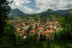 Mountain village seen through trees with peaks. In background, sunny Stock Image