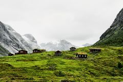 Mountain village with small houses and wooden cabins with grass on the roof in a valley. The huts are standing on green grass and royalty free stock photo