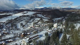 Mountain village and snowy hills in winter, aerial view stock footage
