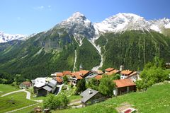 Mountain village with snowy peaks. In the background (Switzerland Stock Images