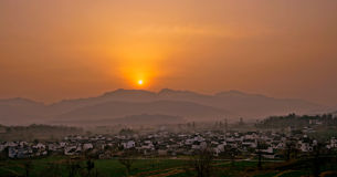 Mountain village at sunset. Sun setting behind a ridge of mountains with a town or village in the foreground valley royalty free stock photo