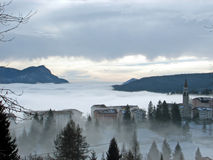Mountain village surrounded by dense fog Royalty Free Stock Photo