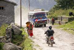 Mountain Village Transport. A scene from a Nepal mountain village showing various forms of transport - women walking carrying items on their head, a motorbike Royalty Free Stock Photo