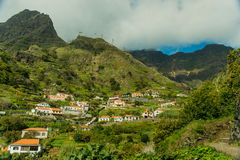Mountain village view. Typical mountain village view of Madeira, Portugal. Tile roofs, white, light yellow and flaxen houses, narrow (tight, restricted) roads royalty free stock images