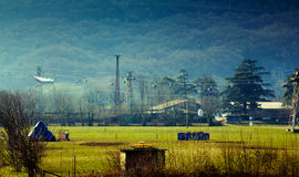 Mountain village. View of a village in the mountains with fields and industrial installations Stock Images