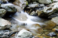 Flowing water. Mountain water flowing between rocks Royalty Free Stock Photo