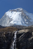 Mountain Waterfall. A rocky waterfall flows in front of the peak of Huandoy in the Peruvian Andes Royalty Free Stock Photo