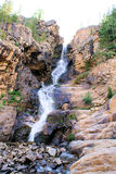 Mountain Waterfall. In the rugged mountains of Utah is the Uintah mountains. This is just one of many waterfalls that has carved out a chasm in the side of the stock image