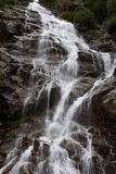 Mountain waterfall. Water flowing down upon the mountain rocks stock photos