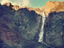 Mountain waterfall in autumn in clear weather. Toned. Mountain waterfall in autumn in clear weather in Almaty Stock Image