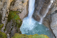 Mountain Waterfall with natural pool. Beautiful mountain waterfalls, moss covered rock ledges, and natural pool at it`s base in the Canadian Rockies Royalty Free Stock Photo