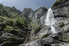 Mountain waterfall seen from below. Refreshing mountain waterfall seen from below, on a clear sunny day, among rocks and alpine trees Royalty Free Stock Image