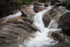 Mountain waterfall among stones . Water mountain stream flowing turbulent stream among stones stock photo