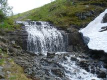 Mountain waterfall in summer in nothern mountains. Mountain waterfall in rocky nothern mountains in Russia in summer at midday Royalty Free Stock Photos