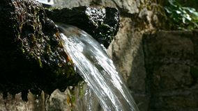 Mountain wellspring. Close-up of the spout of a mountain fountain with crystalline, pure and bright water.Low angle stock video