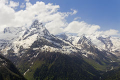 Mountain white peaks of Dombai surrounded by white clouds Royalty Free Stock Images
