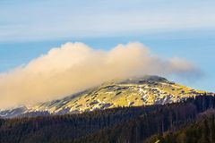 Mountain with white puffy cloud on it.  Royalty Free Stock Image