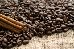 Coffee beans with cinnamon sticks on the background of burlap with empty space for text stock photography