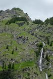 Mountain wiht conifers and waterfall in Bavaria Germany. In vertical format Stock Photography