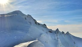 Mountain in winter with sun. Snowy mountain landscape in winter with a distant view of a group of hikers stock photos