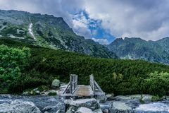 A mountain wooden bridge over the river. stock images
