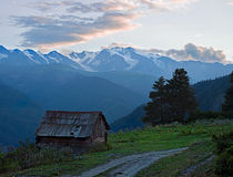 Mountain with wooden hut. Mountain landscape at sunset with wooden hut. Georgia, Svaneti Royalty Free Stock Images