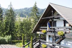 Mountain wooden hut. And villas on a hill with fresh green mountain pastures trees in the background Stock Photos