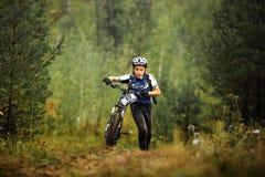 Mountainbike de l'adolescence d'athlète de garçon vers le haut à pied avec sa bicyclette Images stock