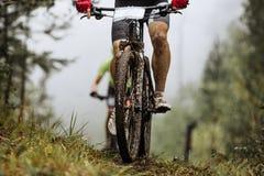 Mountainbike della ruota del primo piano e piedi di cavaliere in spruzzo di sporcizia Fotografia Stock