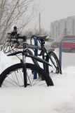 Mountainbike geparkt im Schnee lizenzfreie stockfotos
