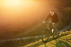 Mountainbikecyklist som rider det enkla spåret på soluppgång, sunt liv Royaltyfri Fotografi