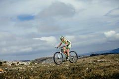 Mountainbiker спортсменки едет на горе против неба на велосипеде Стоковое фото RF