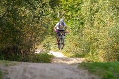 Mountainbiker, der abwärts auf eine Mountainbikebahn im Wald beschleunigt stockfotografie