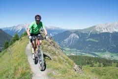 Mountainbiker, der abwärts in Schweizer Alpen reitet Lizenzfreie Stockfotos