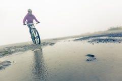 Mountainbiker, der durch Pfütze läuft Stockbild