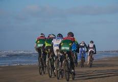 Mountainbiker, die am Strandrennenegmond-pier-c$egmond teilnehmen Stockbilder