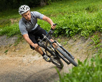 Mountainbiker driving through a steep curve Royalty Free Stock Photography