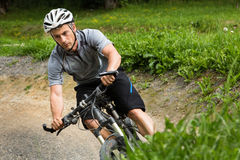 Mountainbiker driving through a steep curve Royalty Free Stock Photos