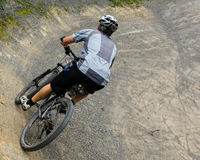 Mountainbiker driving through a steep curve Stock Photo