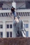 Mountainbiker gör ett jippo främst av den Lenin monumentet Arkivfoto