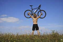 Mountainbiker hob das Fahrrad an Stockfoto